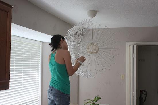 Woman putting flowers on an IKEA MASKROS light