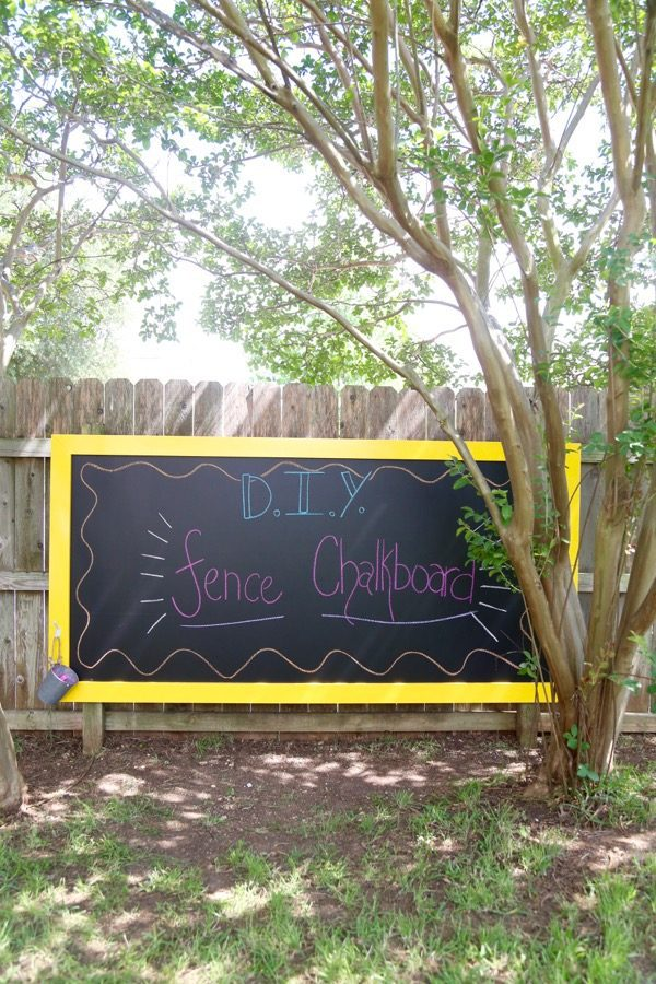 chalkboard hanging on a fence with words written on it - DIY fence chalkboard