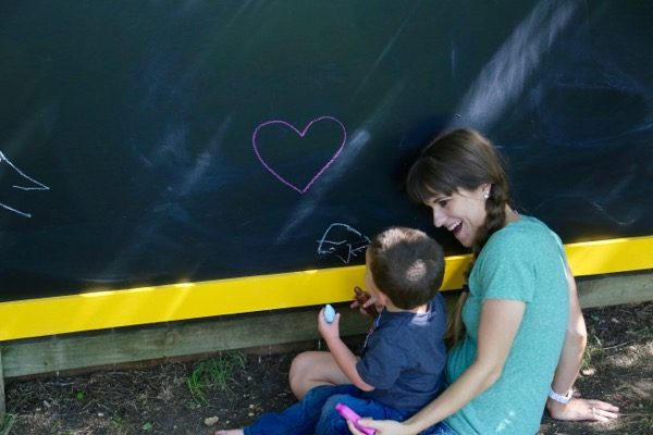 Toddler and mom drawing on outdoor chalkboard