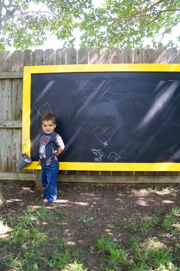 toddler posing in front of a chalkboard hanging on fence