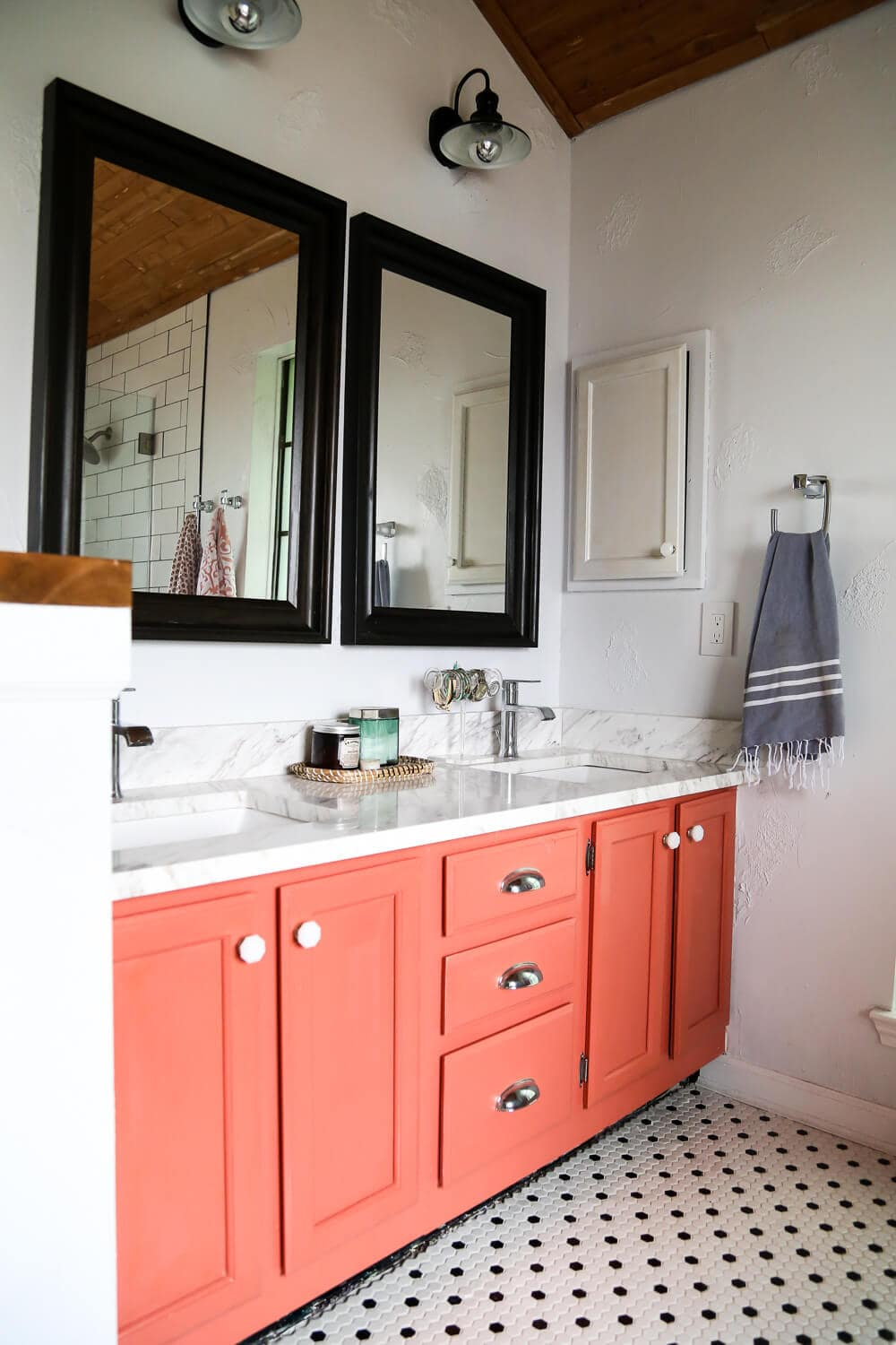 A Master Bathroom Remodel With A Coral Vanity And Black And White Hex Tile  On The