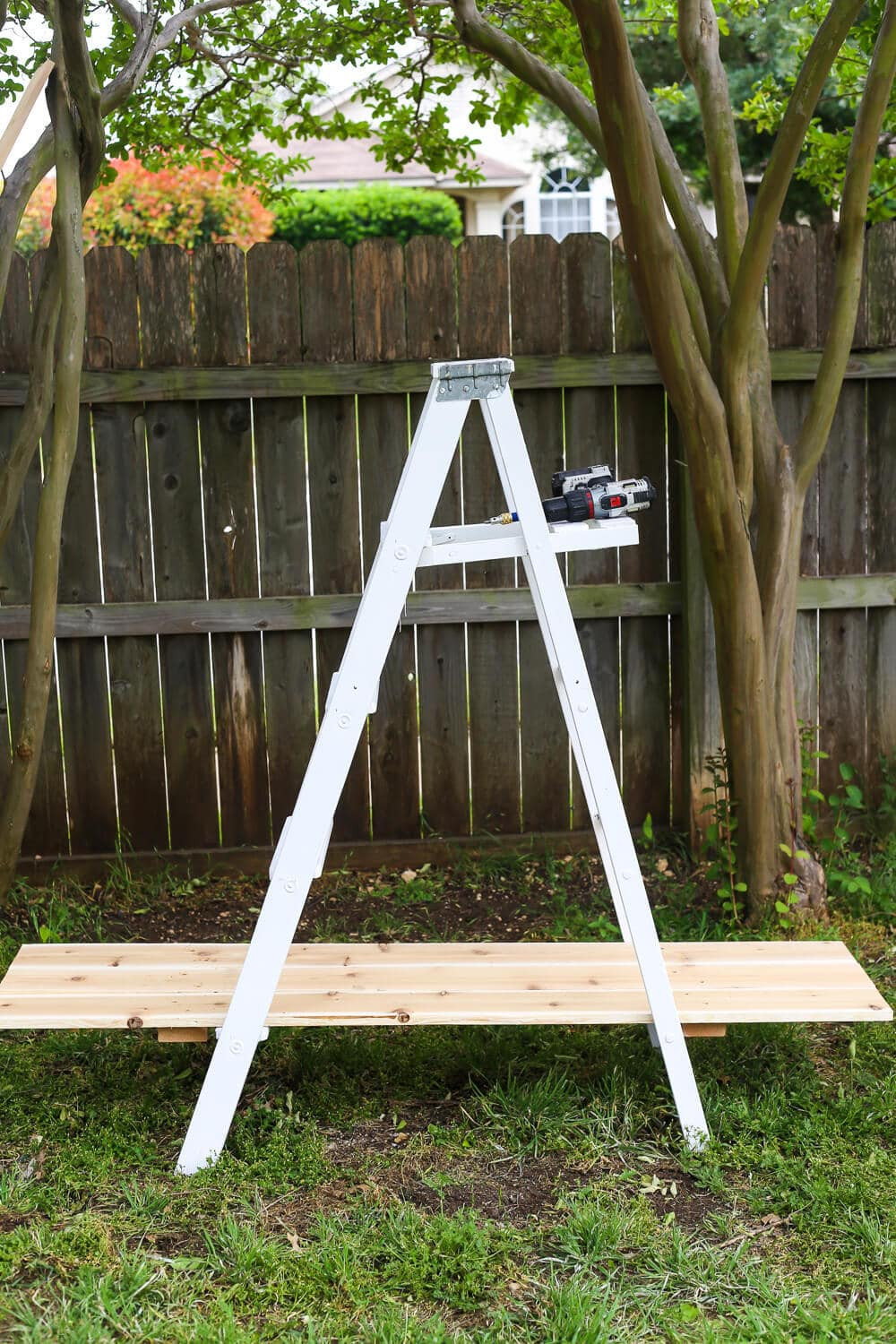 How to quickly and easily build a tiered ladder garden for your backyard. It's so simple, and it looks absolutely gorgeous. Plus, great tips and tricks for planting succulents and other flowers. Fantastic idea for a backyard decoration!