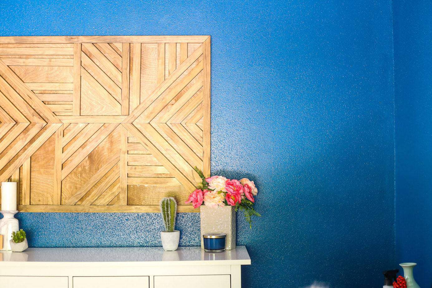 How to create a gorgeous large-scale geometric wood wall art piece for your home. You just need some glue and a saw to cut it down! It's so easy that even a total beginner can do it, and it's absolutely gorgeous!