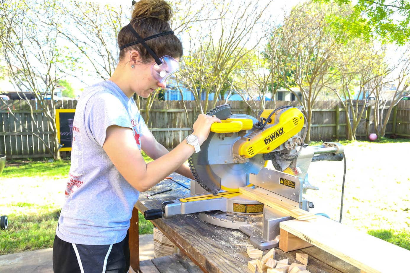 Woman outside using a miter saw on a table