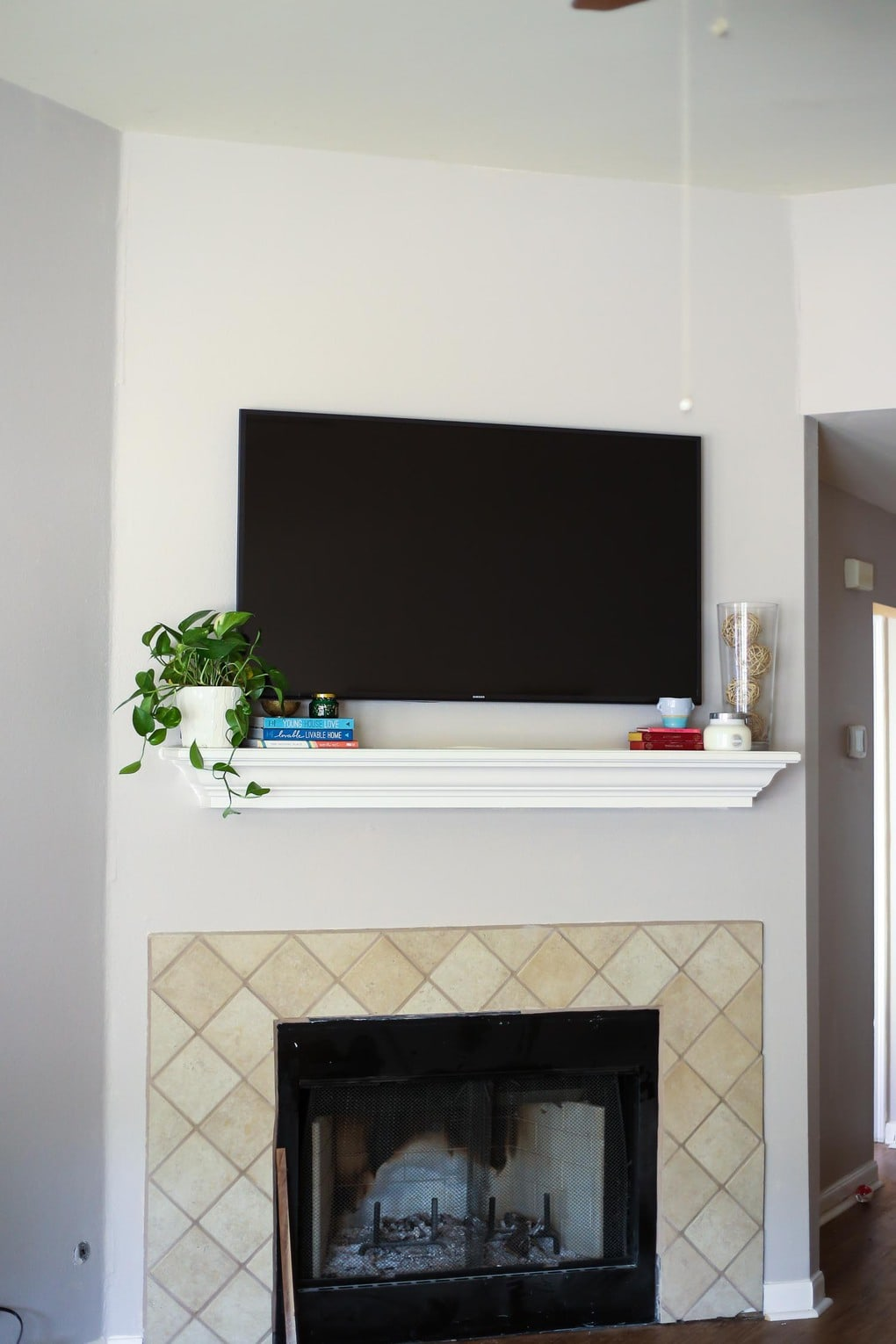 Tips for decorating a mantel when you have a television hanging above it - how to make the most of an awkward setup and make it beautiful!