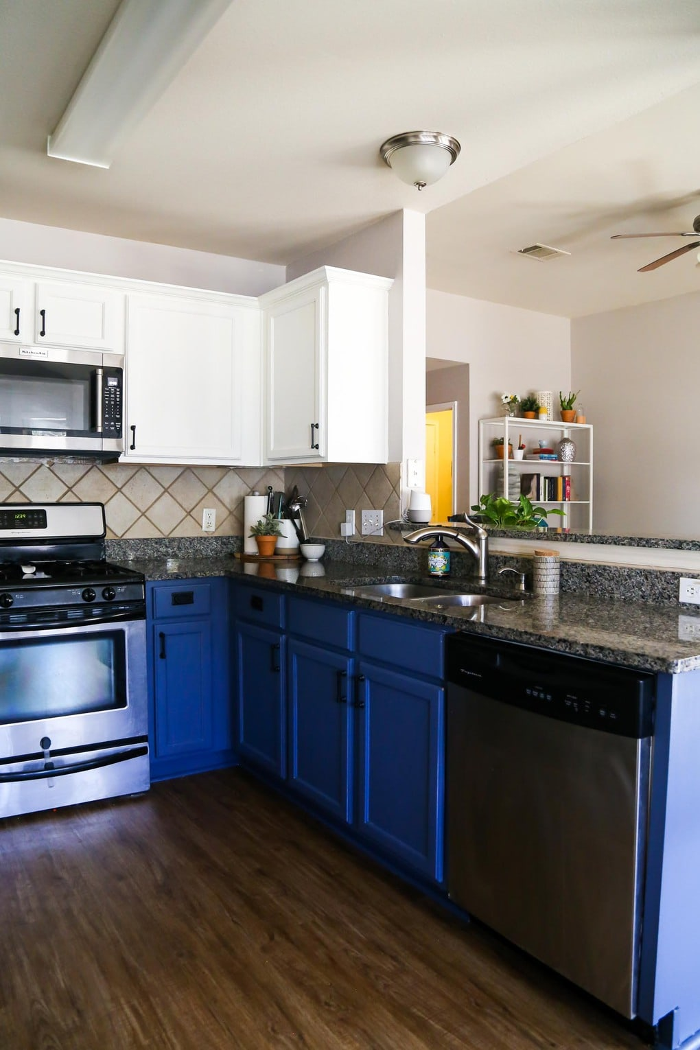 Kitchen with blue and white cabinets and Mohawk vinyl plank flooring on the floor