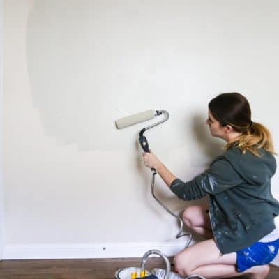 Woman painting a gray wall using a power roller