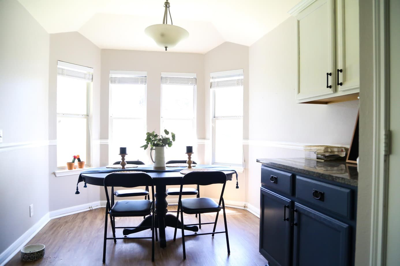 Small dining room with black table and four chairs