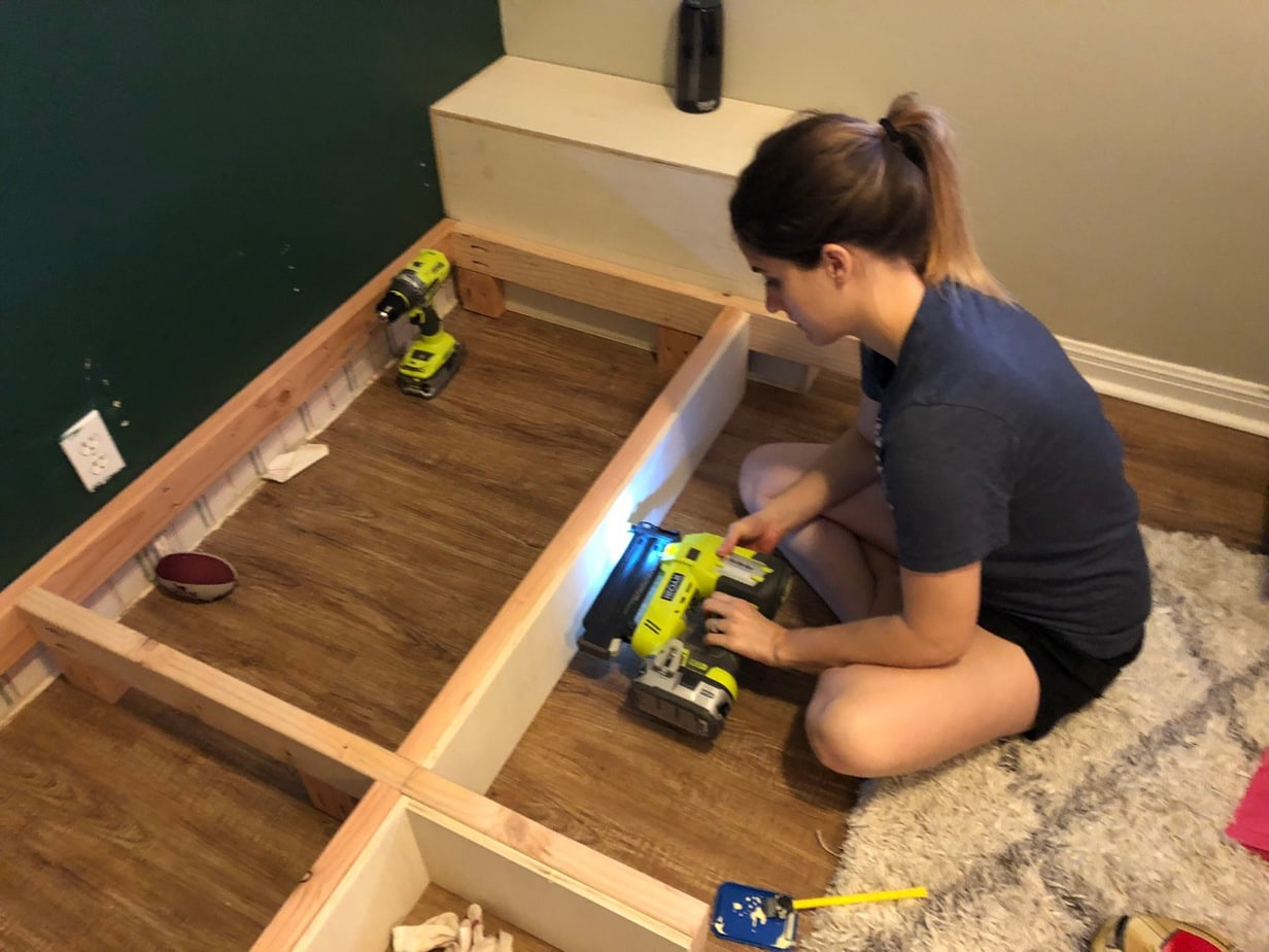Woman nailing plywood to framing for DIY built in shelves