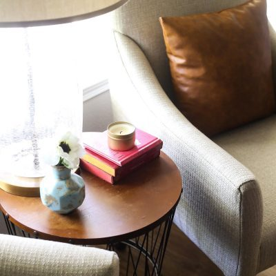 Round side table with books, a lamp, and a candle