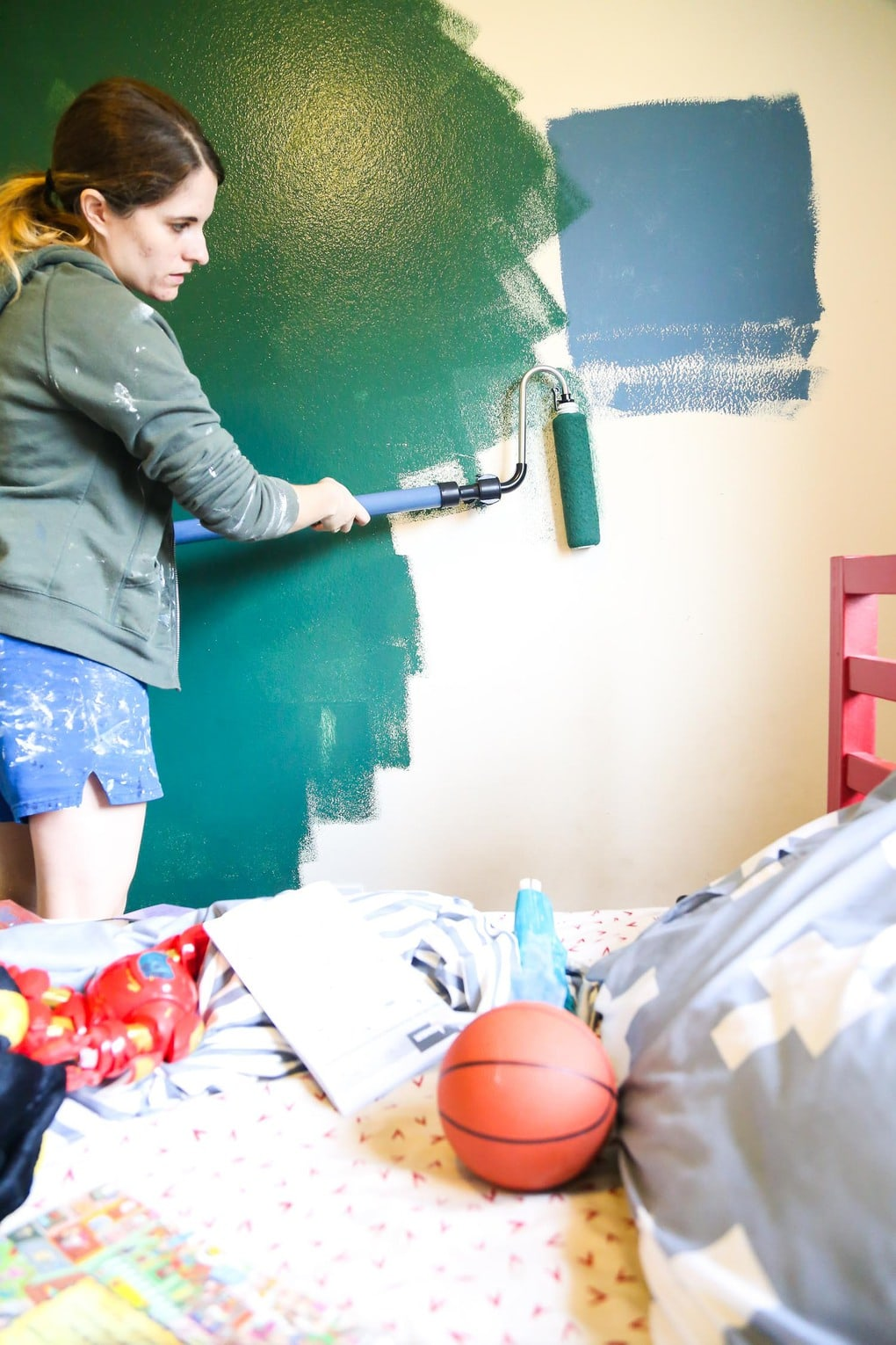 Woman painting a green accent wall using a Wagner Smart Roller