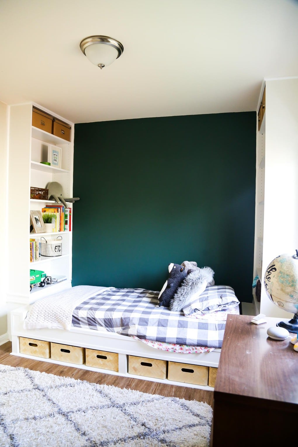 Build in shelves with a bed that has grey bedding and a green accent wall
