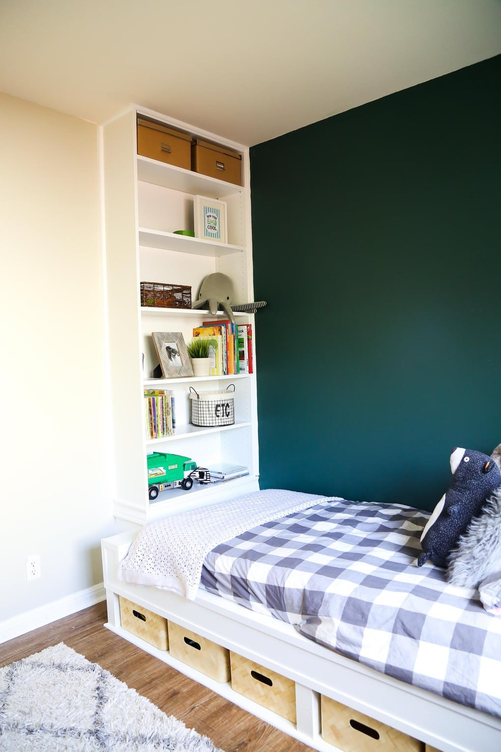 White built in bed and bookcase with grey bedding and green wall