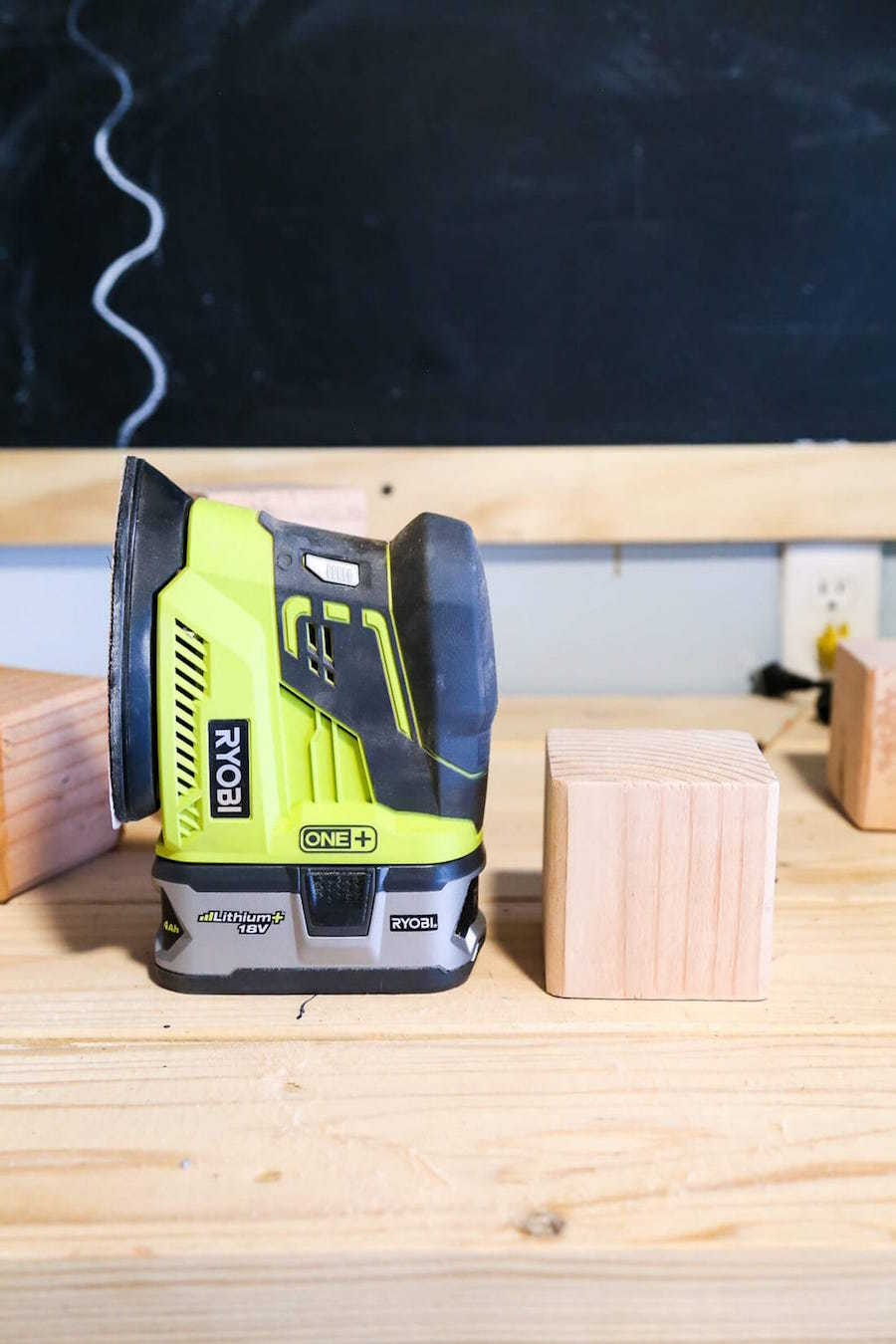unfinished wood dice next to a power sander