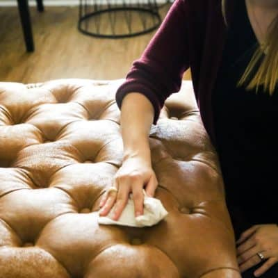 Woman cleaning leather ottoman with Mohawk leather cleaner
