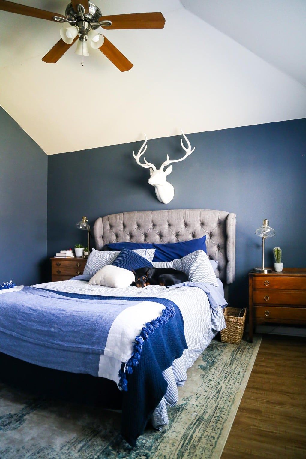 A master bedroom with dark blue walls, blue bedding, and Mohawk vinyl plank flooring