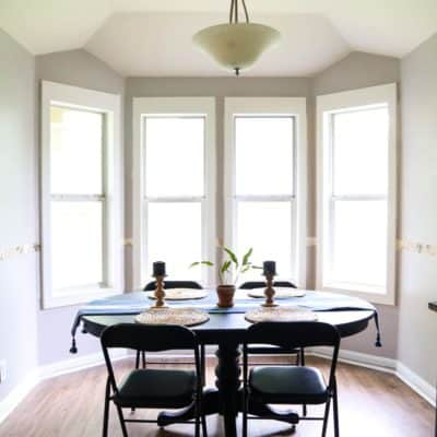 Dining room with DIY window trim and a hidden trash can