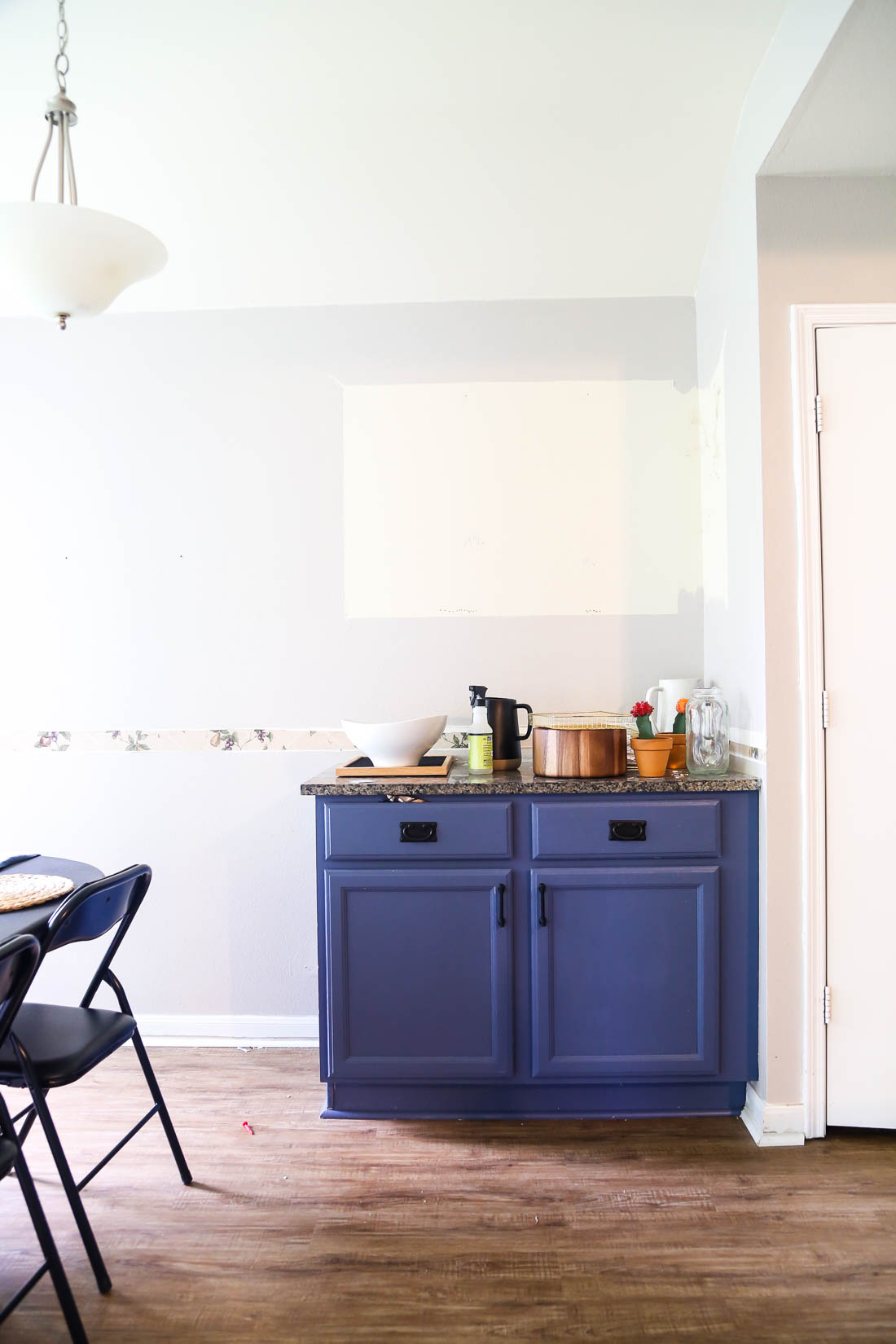 This blue kitchen cabinet has a hidden trash can!