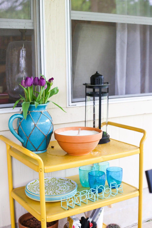 Yellow backyard bar cart with blue decor