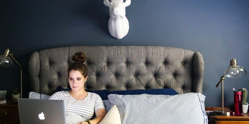 woman sitting on a bed with laptop