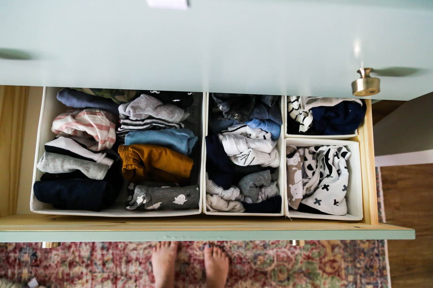 organizing clothes in nursery dresser