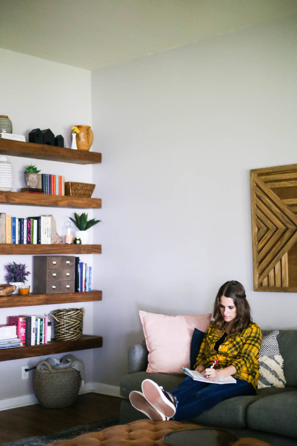 living room with floating shelves and woman on sofa