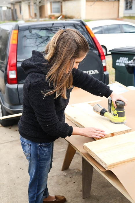 Woman sanding DIY bathroom shelves