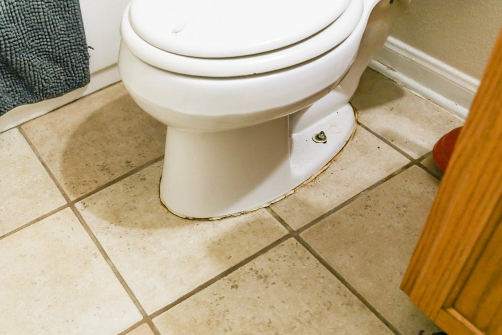 close-up of toilet with stained and cracking grout at base