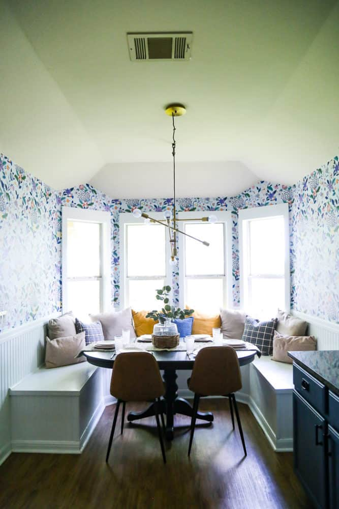 Dining room with built in banquette seating and floral wallpaper