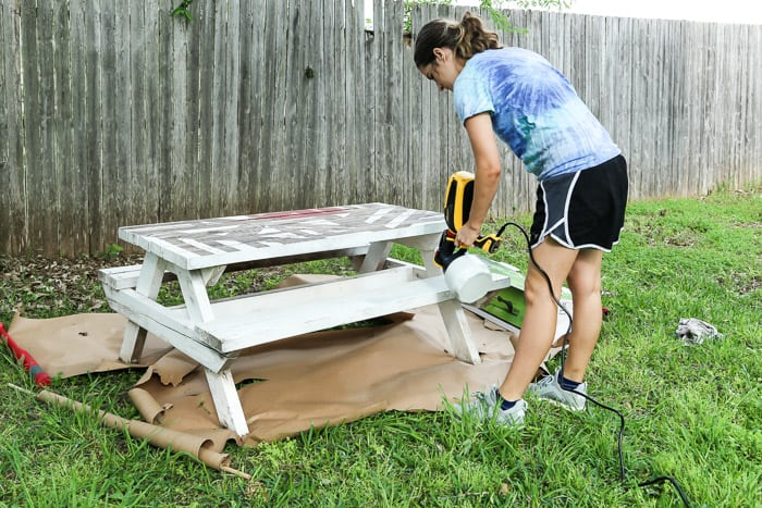 woman using paint sprayer to paint a picnic table