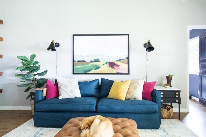 living room with a blue sofa, landscape art, and black sconces