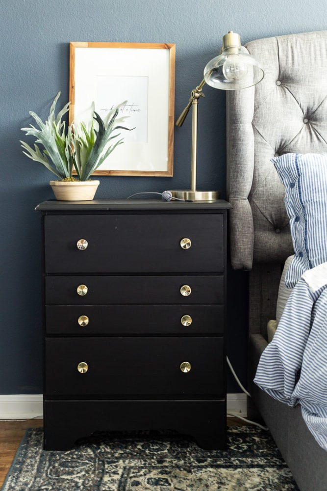 Black dresser used as a nightstand