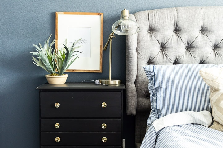 Black dresser sitting in front of a blue wall