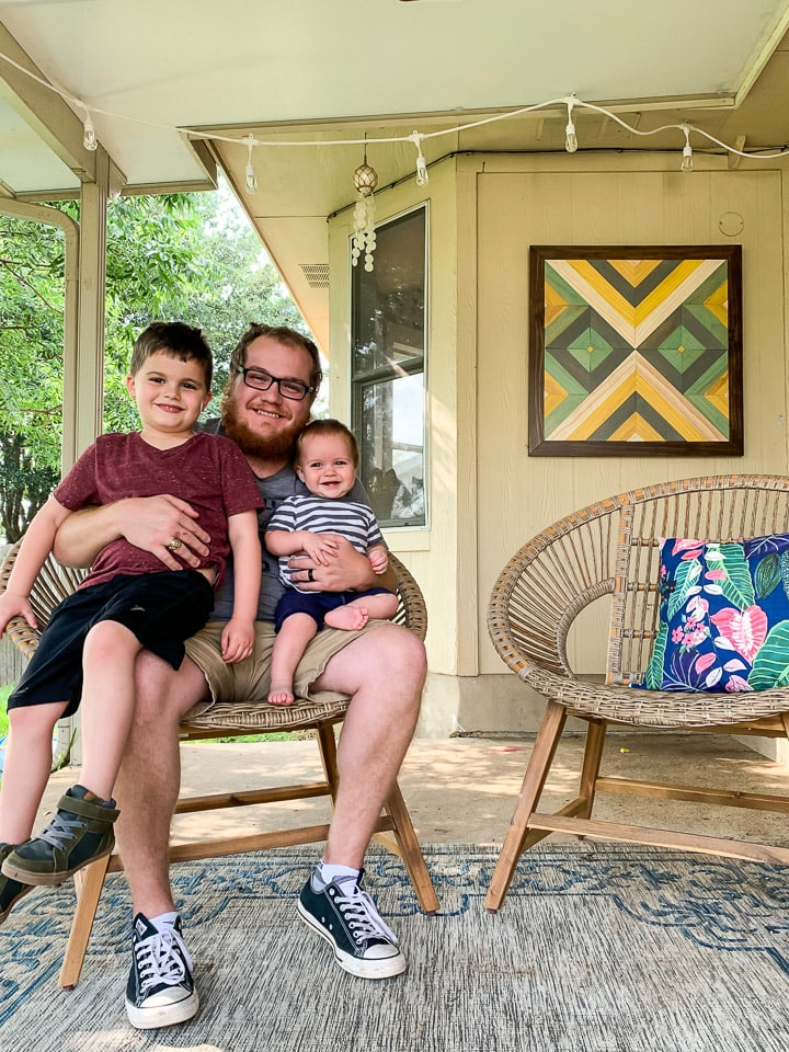 man sitting on a patio with his two young sons