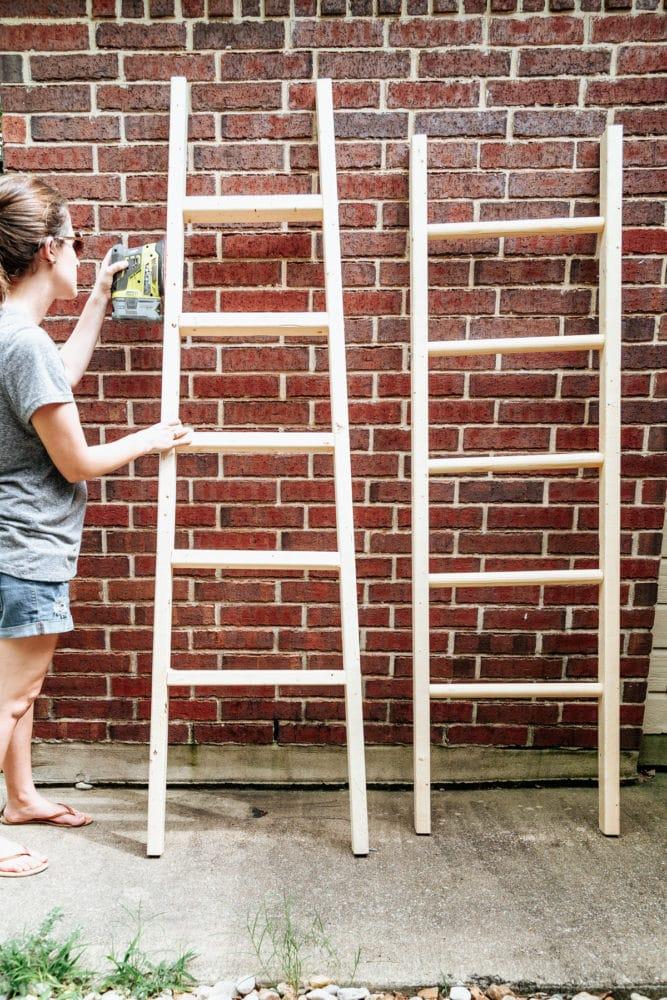 woman sanding a DIY blanket ladder