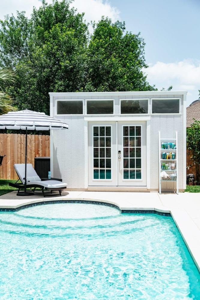 serene backyard with a pool and pool house