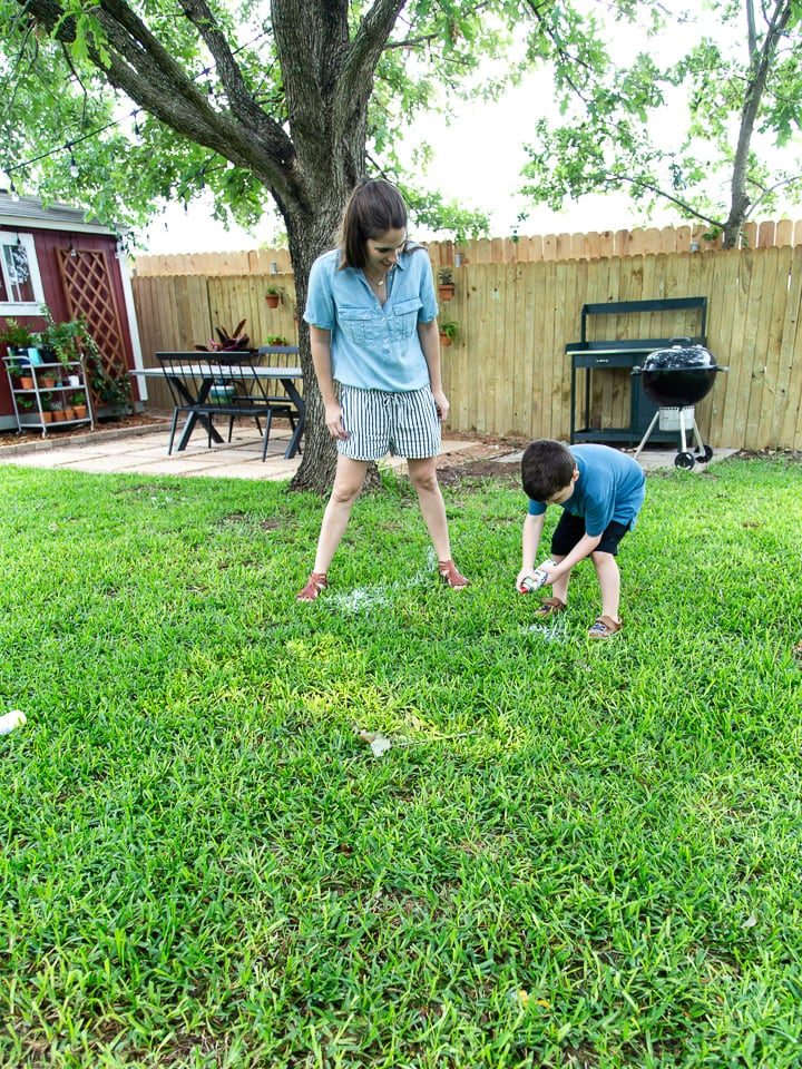A mom and her young son playing Pictionary in the grass using spray chalk