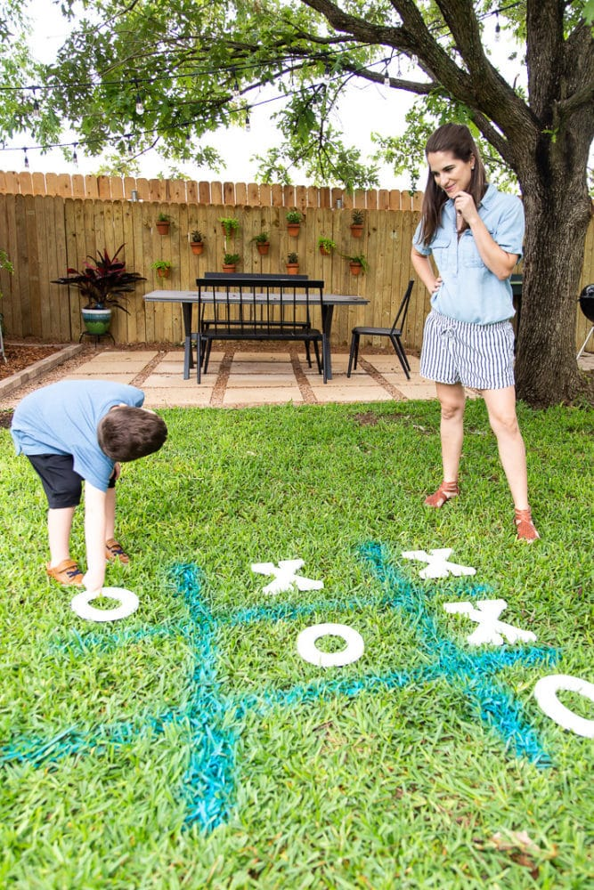 a mom and her young son playing tic tac toe in the grass using spray chalk