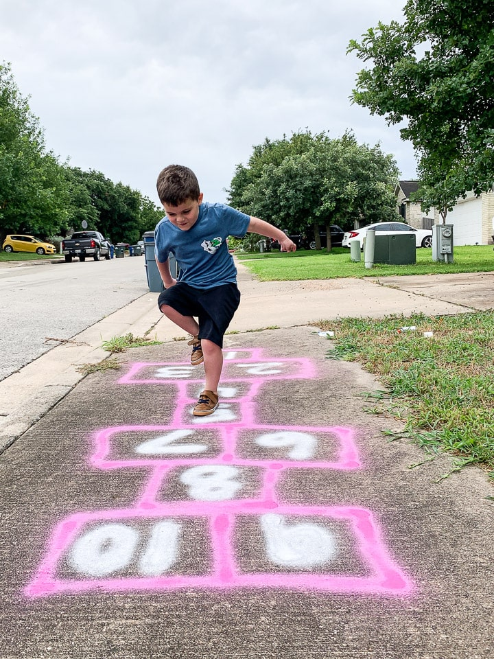 young boy playing hopscotch on the sidewalk