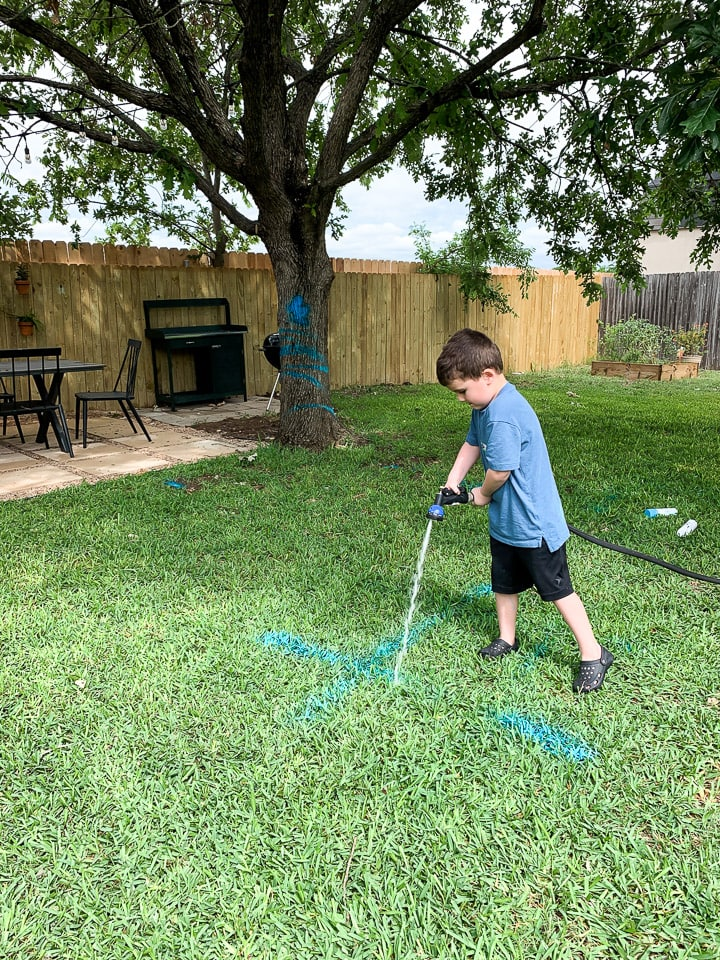 a young boy cleaning up spray chalk using a water hose