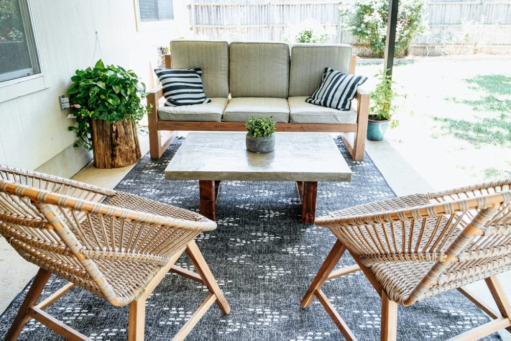 back porch with DIY outdoor sofa, a DIY coffee table, and two lounge chairs