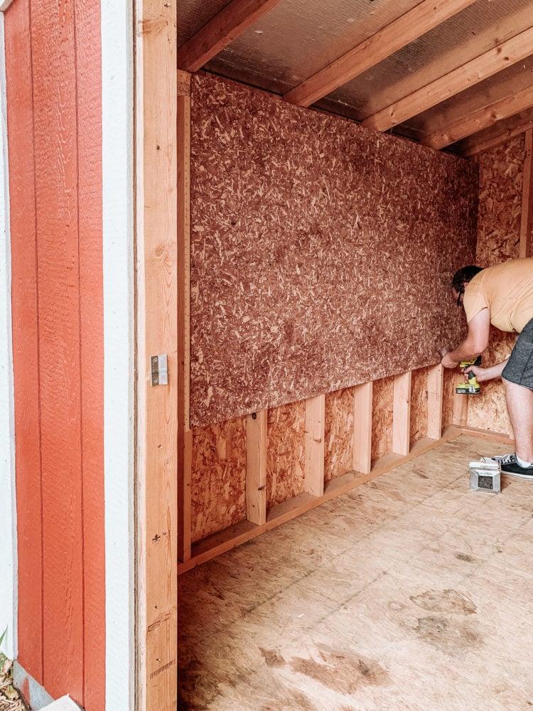 man installing cedar flakeboard panels