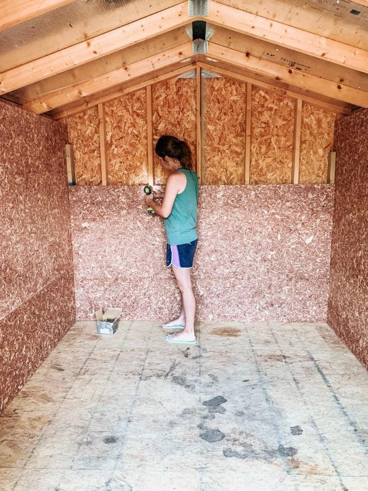 woman installing cedar flakeboard panels