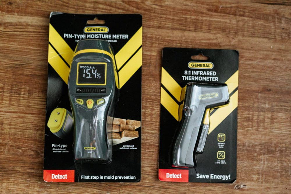 a General Tools pin-type moisture meter sitting on the ground with a General tools infrared thermometer
