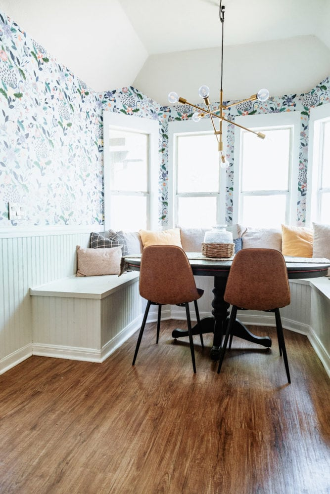 a dining room with floral wallpaper and a built-in bench
