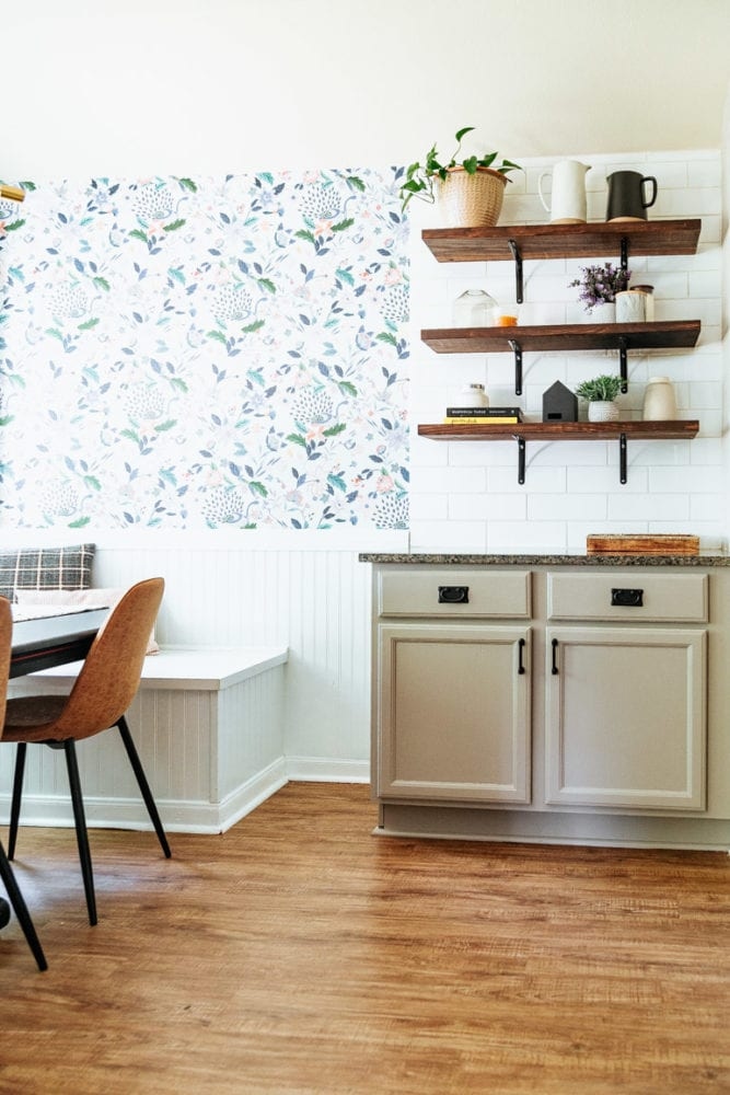 a kitchen and dining room with wallpaper, open shelving, and beige cabinets