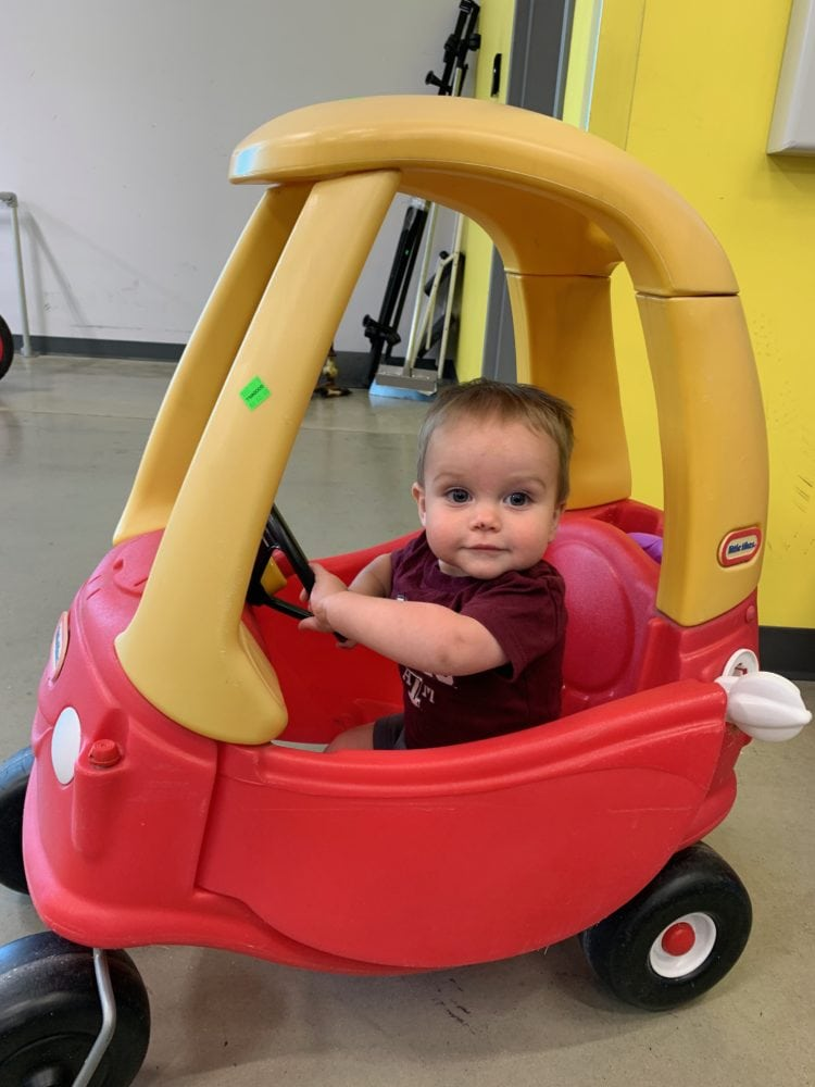small toddler in a Cozy Coupe car