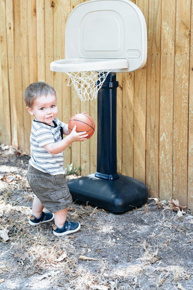 toddler playing with a little tikes basketball hoop