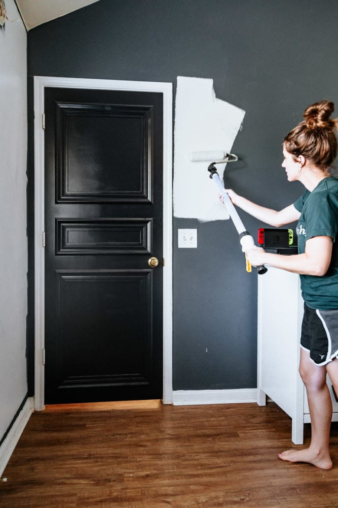 woman painting a wall white
