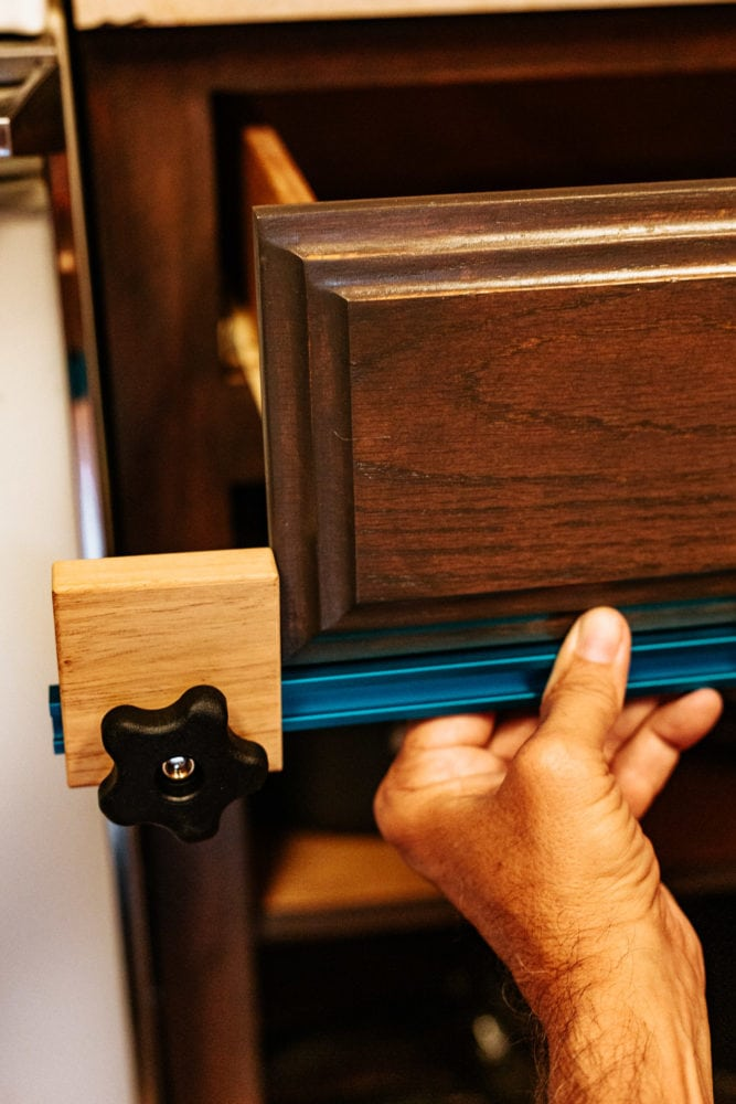 man using Rockler jig to install cabinet hardware